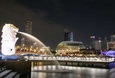 Den Merlion statyspringbrunnen i Merlion parkerar och Singapore stadshorisont på natten Arkivfoto