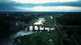Den mest breda vattenfallet i Europa i Lettland Kuldiga och tegelstenbro över flodVenta det Areal Dron skottet stock video
