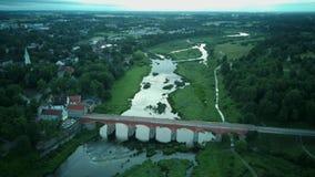 Den mest breda vattenfallet i Europa i Lettland Kuldiga och tegelstenbro över skottet för dron för flodventa det areal lager videofilmer