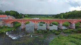 Den mest breda vattenfallet i Europa i Lettland Kuldiga och tegelstenbro över skottet för flodVenta det areal dron arkivfilmer