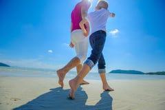 Den mest lyckliga barndomen: fader och son som promenerar den tropiska stranden Arkivfoto