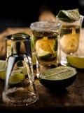 Den mexicanska guld- tequilaen med limefrukt och saltar på trätabellen royaltyfria foton
