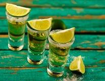 Den mexicanska guld- tequilaen med limefrukt och saltar på trätabellen arkivbilder