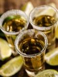 Den mexicanska guld- tequilaen med limefrukt och saltar på trätabellen royaltyfri bild