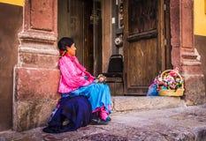 Den mexicanska kvinnan med traditionellt sälja för klänning handcrafts Arkivbilder