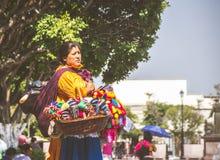 Den mexicanska kvinnan med traditionellt sälja för klänning handcrafts Royaltyfri Foto