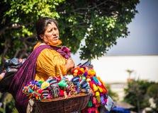 Den mexicanska kvinnan med traditionellt sälja för klänning handcrafts Arkivbild