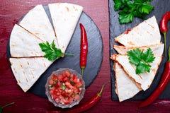 Den mexicanska quesadillaen med salsa på svart kritiserar stenplattan på röd träbakgrund vattenfärgmålning på vit bakgrund Top be royaltyfria bilder