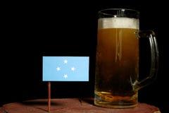 Den Micronesian flaggan med öl rånar isolerat på svart arkivbilder