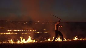Den militära mannen visar kapacitet med svärd på brasor 4K stock video