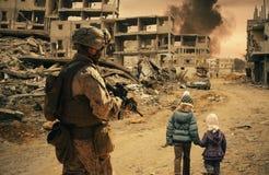 Den militära soldaten följer två hemlösa flickor royaltyfri bild