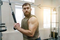 Den militära sporten, den muskulösa caucasianen uppsökte den vuxna mannen som gör övningar i den iklädda idrottshallen en skottsä royaltyfri bild