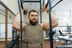 Den militära sporten, den muskulösa caucasianen uppsökte den vuxna mannen som gör övningar i den iklädda idrottshallen en skottsä royaltyfri fotografi