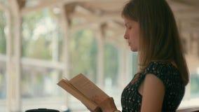 Den Millennial damen läser ett boksammanträde på det väntande på drevet för bänken på semester arkivfilmer