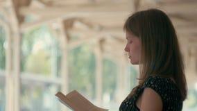 Den Millennial kvinnan läser en bok på det väntande på drevet för stationsplattformen stock video