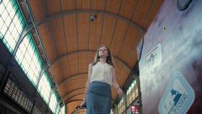 Den Millennial kvinnan väntar på avvikelse av hennes drev, medan gå på station stock video
