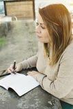 Den Millennial latinamerikanska flickan skriver ner hennes mål i en tidskrift i ett utomhus- kafé royaltyfria foton