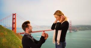 Den Millennial pojkvännen föreslår till flickvännen framme av Golden gate bridge arkivfoton