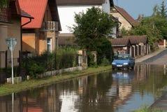 Den milt översvämmade gatan och bilen, är det den soliga stormen arkivfoto
