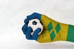 Den mini- bollen av fotboll i den helgonVincent flaggan målade handen på vit bakgrund Begrepp av sporten eller leken i handtag el arkivfoto