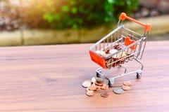 Den Mini Shopping Cart eller spårvagn- och exponeringsglaskruset fyllde med mynt som isolerades på en tabell som för återförsäljn arkivbild