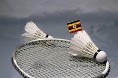 Den Mini Uganda flaggapinnen på den pålagda fjäderbollen det netto av badmintonracket och fokuserar ut en fjäderboll fotografering för bildbyråer