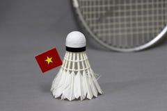 Den Mini Vietnam flaggapinnen på den vita fjäderbollen på den gråa bakgrunden och fokuserar ut badmintonracket fotografering för bildbyråer