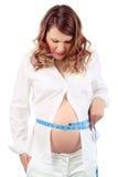 Den missbelåtna gravid kvinna mäter buken Arkivfoton
