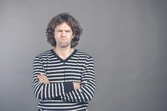Den misshog Closeupståenden, den ilskna vresiga mannen i dålig inställning för randig tröja, armar korsade, vikt och att se dig,  royaltyfri foto