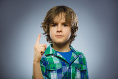 Den missnöjda ilskna pojken med hotar fingret som isoleras på grå bakgrund arkivfoto