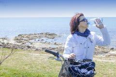 Den mitt- åldriga sunda kvinnan med bevattnar buteljerar på mountainbiket Royaltyfri Bild