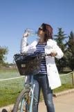 Den mitt- åldriga sunda kvinnan med bevattnar buteljerar på mountainbiket Fotografering för Bildbyråer