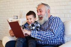 Den mitt- sidan sköt av upprymd granfather och hans son, medan läsa ett s royaltyfria foton