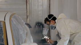 Den mitt- skottarbetaren målar en bil i vit färg arkivfilmer