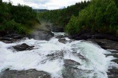 Den mjölkaktiga vita massiva långa hala dalen för vattenfallet vaggar ner och stenar i sommar Arkivbild