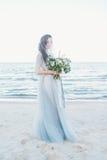 Den mjuka bruden skyler in med bröllopbuketten vid havet Fotografering för Bildbyråer