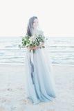 Den mjuka bruden skyler in med bröllopbuketten vid havet Royaltyfri Bild