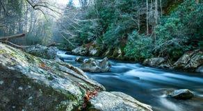 Den mjuka flödande floden med vaggar Royaltyfria Bilder
