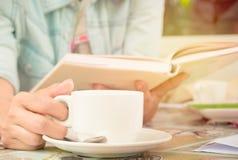 Den mjuka fokusen, slut av kvinnlign räcker upp den hållande koppen kaffe och nolla Arkivfoto