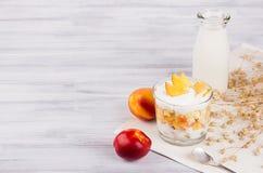 Den mjuka frukosten med havreflingor, skivapersikan och mjölkar flaskan på det vita wood brädet Royaltyfria Foton