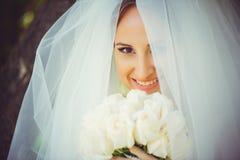 Den mjuka lyckliga bruden skyler in, den lyckliga kvinnan i bröllopsklänning med buketten i händer, vit skyler räkningar vänder m Arkivbild