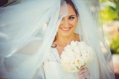 Den mjuka lyckliga bruden skyler in, den lyckliga kvinnan i bröllopsklänning med buketten i händer, vit skyler räkningar vänder m Arkivfoton