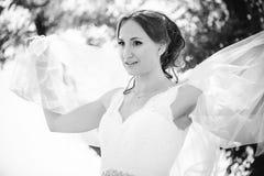 Den mjuka lyckliga bruden skyler in, den lyckliga kvinnan i bröllopsklänning med buketten i händer, vit skyler räkningar vänder m Royaltyfri Bild