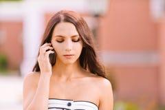 den mobila telefonen talar kvinnabarn Arkivbild