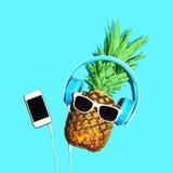 Den modeananassolglasögon och hörlurar lyssnar till musik på smartphonen arkivfoton