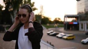 Den moderiktiga attraktiva flickan i stilfull ungdom beklär fritt att dansa utanför på gatan Lyssna till musiken i svart stock video