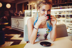 Den moderiktiga flickan med ljust kulört hår som sitter i kafé, drinkkaffe och, äter efterrätten royaltyfri foto