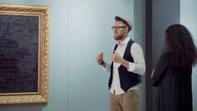 Den moderiktiga konstnären förklarar idé av hans bild för kvinnlig besökare av utställningen lager videofilmer