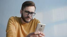 Den moderiktiga mannen använder mobiltelefonen för kommunikation lager videofilmer