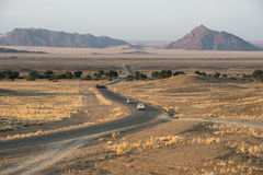 Den moderna asfaltvägen med bilar böjer över namibiska fält Royaltyfria Bilder